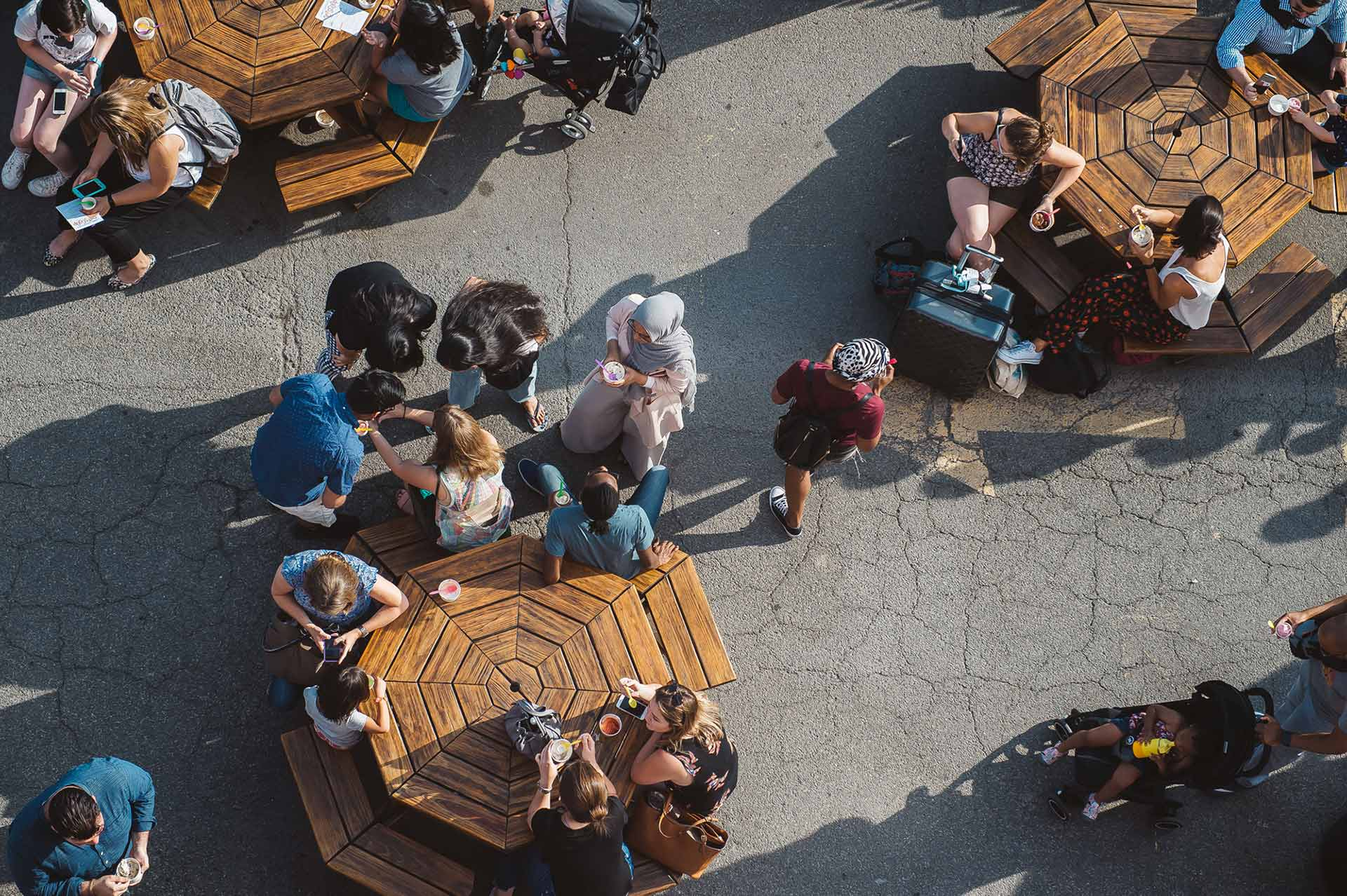 view from above of people dining outside at three round tables