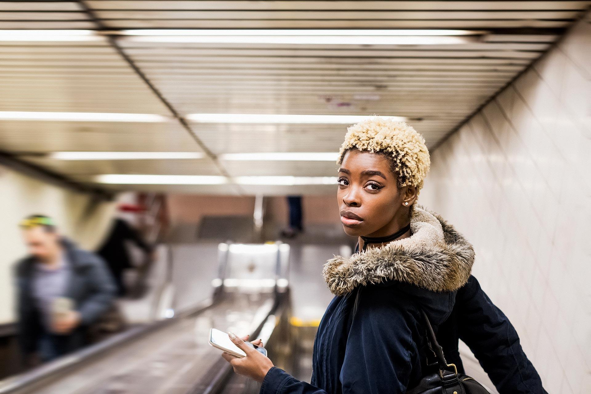 woman wearing fur collared coat on escalator