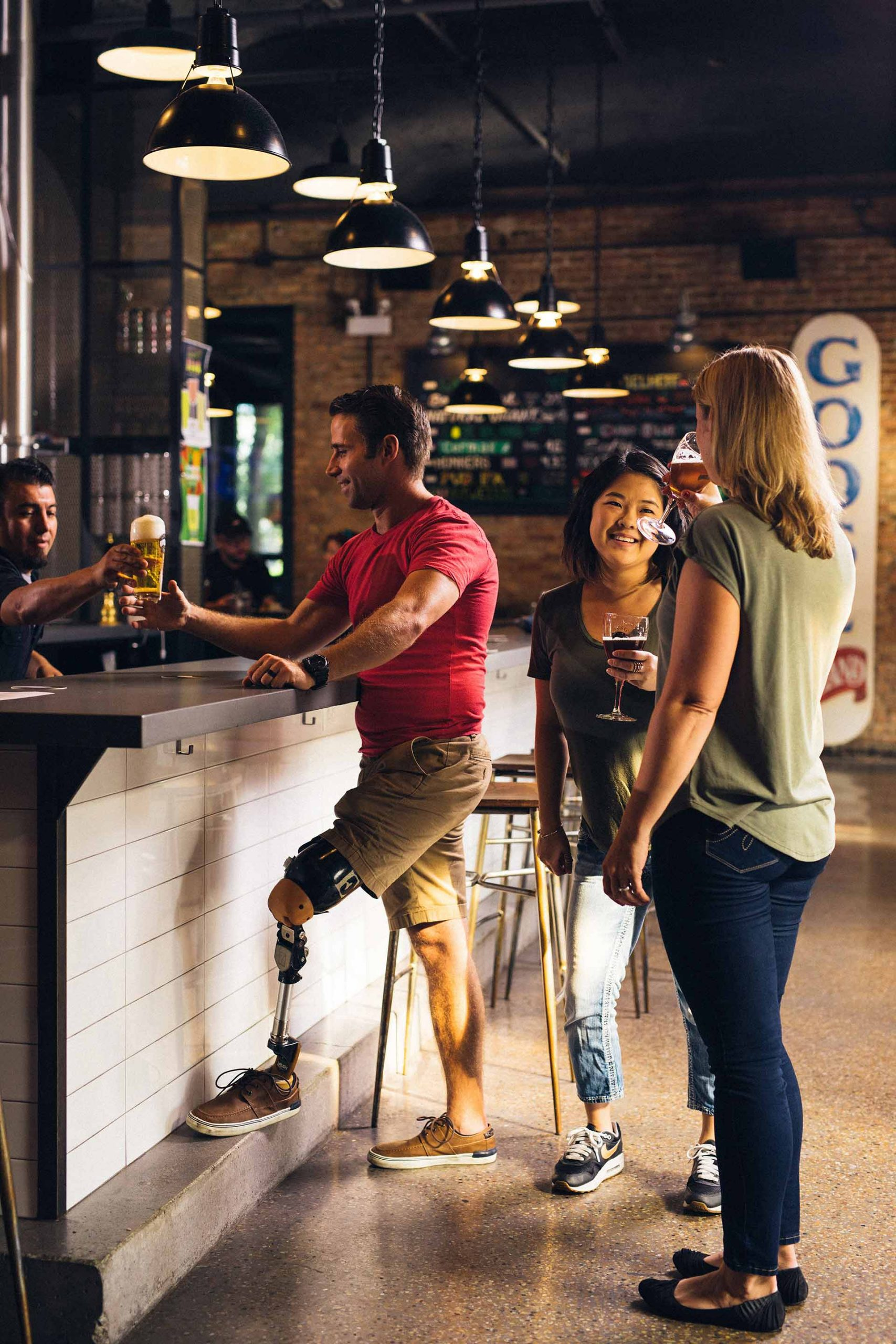 man with prosthetic leg buying beer with two women drinking wine at a bar