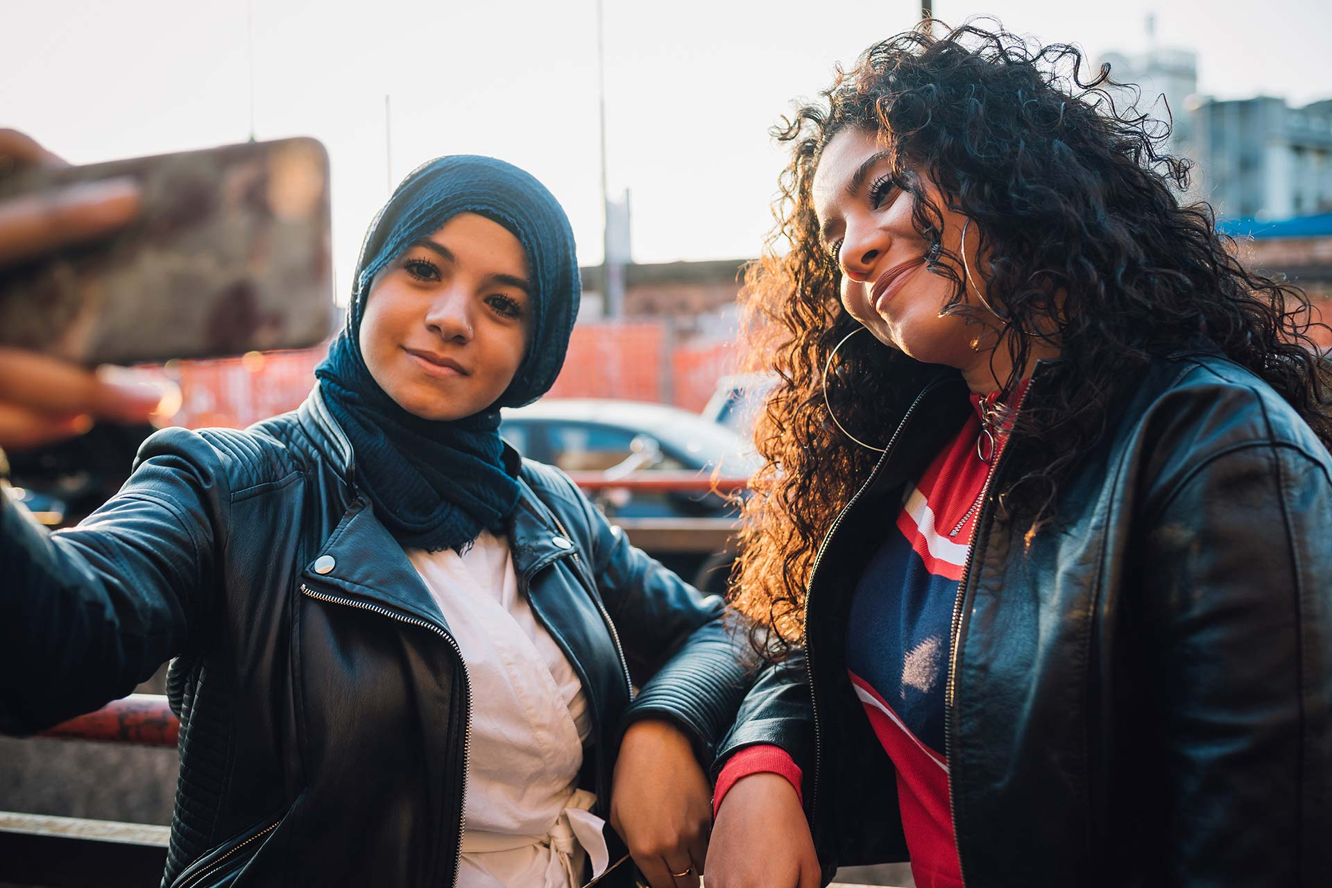 woman in headscarf and woman with long curly hair taking selfie