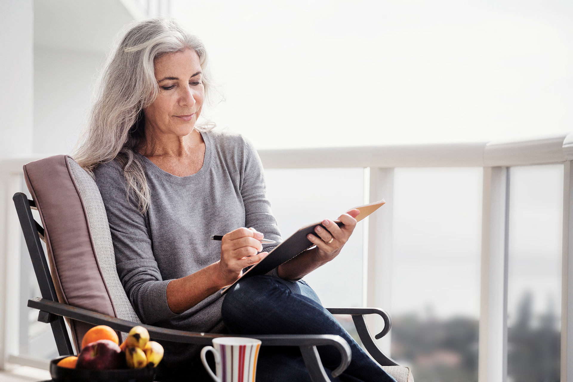woman with long silver hair writing in journal on balcony