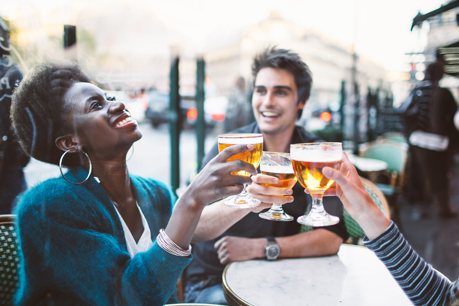three people drinking beer outside smiling