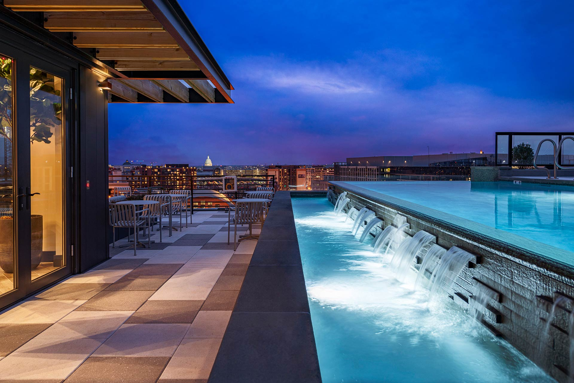 infinity pool with waterfall overlooking city at night