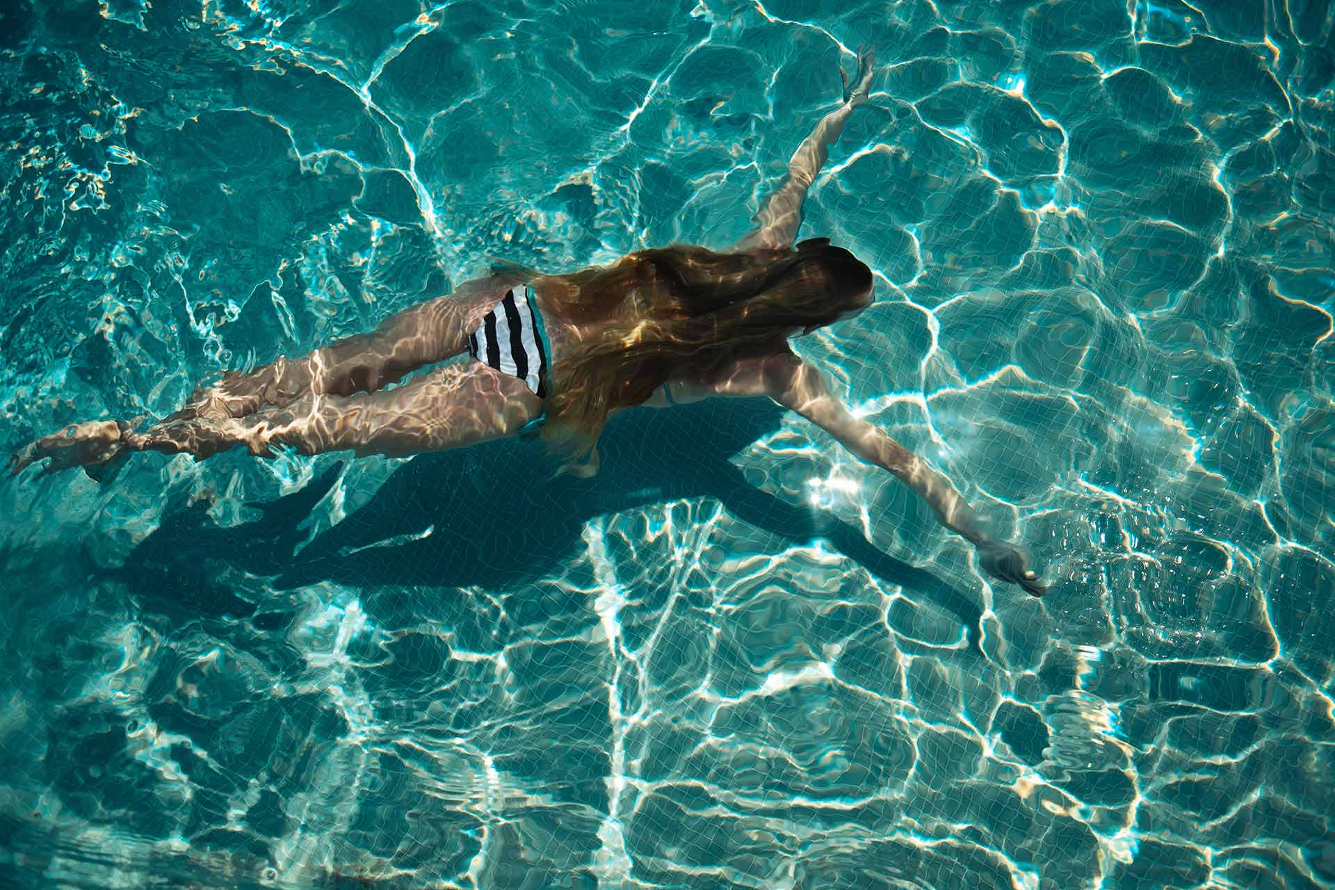 view from above of woman swimming underwater