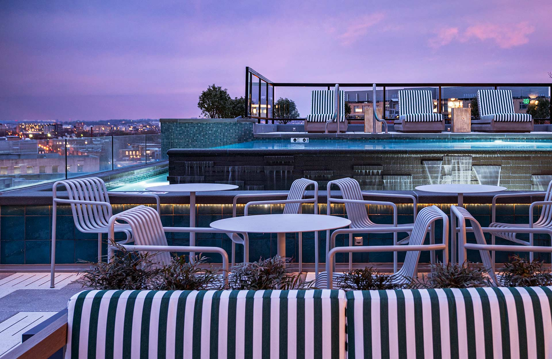 outdoor rooftop seating in front of infinity pool at dusk
