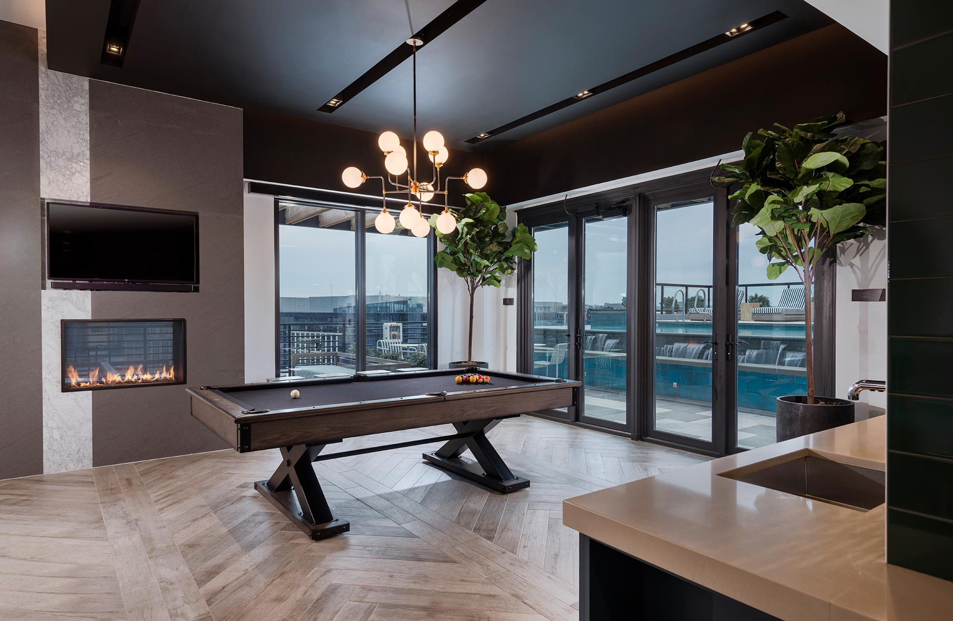 billiards table next to fireplace and television