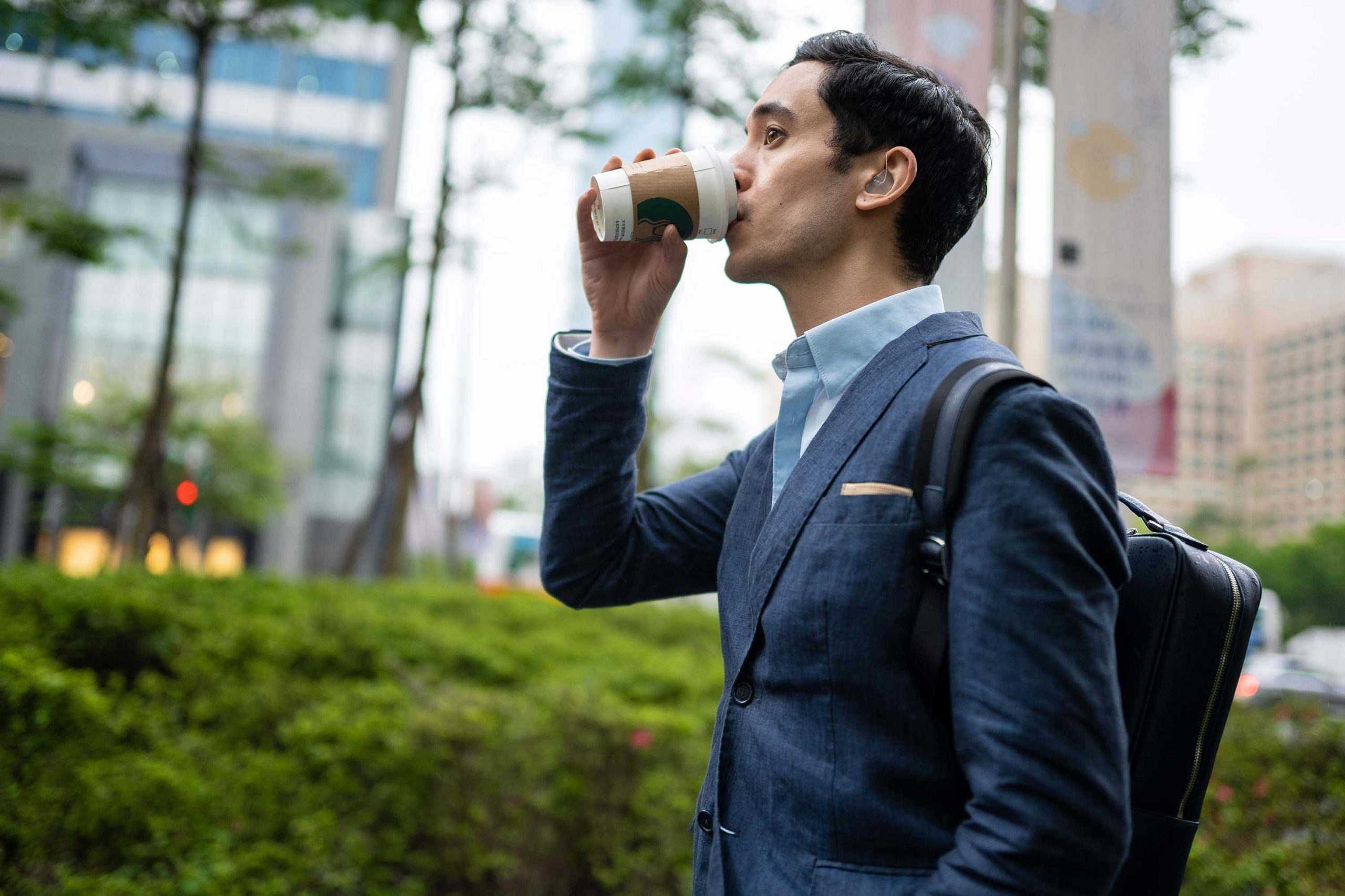 man in suit walking and drinking coffee